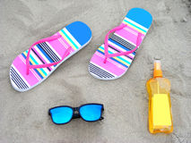 Flip-flops, sunglasses and sun-care milk. On a sandy beach Royalty Free Stock Photography