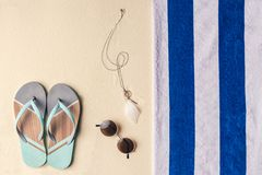 Flip flops and sunglasses by towel. On light sand royalty free stock images
