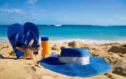 Flip flops, sunscreen, hat and starfish on sandy beach Royalty Free Stock Photos
