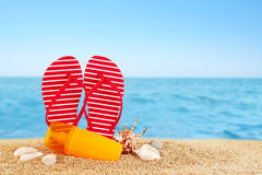 Flip-flops and sunscreen spray on the beach. Royalty Free Stock Image