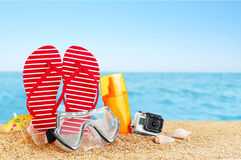 Flip-flops, sunscreen spray and diving masks on the beach. Royalty Free Stock Photo