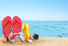 Flip-flops, sunscreen spray and diving masks on the beach. Stock Photography