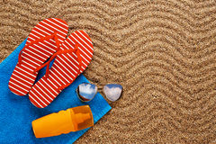 Flip-flops, sunscreen spray and towel on the beach. Royalty Free Stock Photography