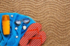 Flip-flops, sunscreen spray and towel on the beach. Sunglasses and shells royalty free stock images