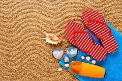 Flip-flops, sunscreen spray and towel on the beach. Royalty Free Stock Image