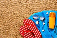 Flip-flops, sunscreen spray and towel on the beach. Royalty Free Stock Images