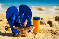 Flip flops, sunscreen and starfish on sandy beach Stock Photos