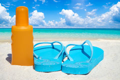 Flip flops and suntan lotion. Blue Flip flops a bootle suntan lotion on the sunny beach Stock Photo