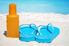 Flip flops and suntan lotion. Blue Flip flops a bootle suntan lotion on the sunny beach Stock Images