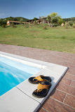 Flip-flops swimming-pool. Flip-flops on the border of the swimming-pool of a luxury country house in the famous tuscan hills, Italy royalty free stock images