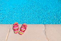 Flip flops at the swimming pool. Colorful striped flip flops at the swimming pool stock images