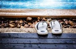 Flip-flops by the swimming pool. Men`s flip-flops by the swimming pool,shallow DOF stock photos