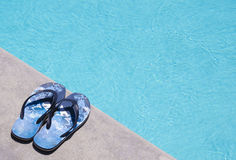 Flip-flops by the swimming pool. Men's flip-flops by the swimming pool in sunny day Royalty Free Stock Photography