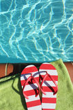 Flip flops by swimming pool side Royalty Free Stock Image