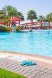 Flip flops at at the swimming pool. Flip flops at at the tropical swimming pool area Royalty Free Stock Photo