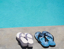 Flip-flops by the swimming pool. Women's and men's flip-flops by the swimming pool in sunny day Stock Image