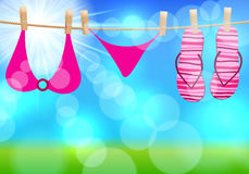 Flip-flops and swimsuit hanging on a rope Royalty Free Stock Photo