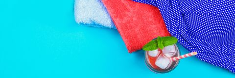 Flip-flops, swimsuit, towel and ice cocktail on a blue pastel background. Rest, travel. Top view. Copy space. Flat lay. Flip-flops, swimsuit, towel and ice royalty free stock images
