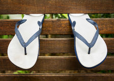 Flip Flops. Or thongs hanging from a wooden wall at a beach resort royalty free stock photos