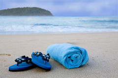 Flip flops and towel on the beach Stock Photos