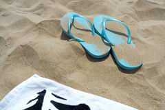 Flip flops and towel on the beach Stock Image