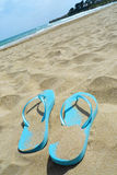 Flip flops and towel on the beach Royalty Free Stock Image