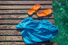 Flip-flops and towel on the jetty Royalty Free Stock Photos