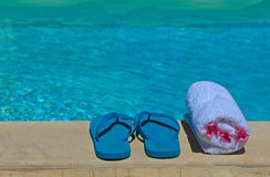 Flip flops and towel by swimming pool Stock Photos