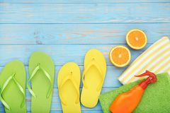 Flip flops with towels and cosmetic bottle. On wooden table royalty free stock photography
