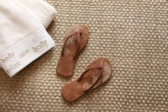 Flip flops with towels on seagrass rug Royalty Free Stock Photos