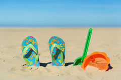 Flip flops and toys at the beach. Flip flop and plastic toys at the summer beach Royalty Free Stock Photos