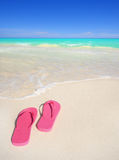 Flip flops on tropical beach. A pair of pink flip flops on a gorgeous tropical beach. Travel & Vacation Collection stock image
