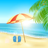 Flip flops and umbrella on the beach Stock Images