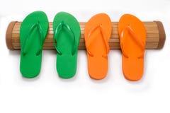 Flip Flops verde y anaranjado en Mat With Copy Space de bambú Imagen de archivo