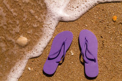 Flip Flops in the water. Pair of purple flip flops laying on the sand with ocean wave washing up on the beach Royalty Free Stock Images