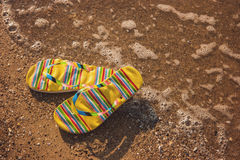 Flip flops on wet sand. Footwear on seashore. Feel the warmth of sea. Vacation at the tropical island royalty free stock photo