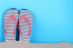 Flip flops in a white and blue strip in the sand on a blue background. With a place for an inscription royalty free stock photos