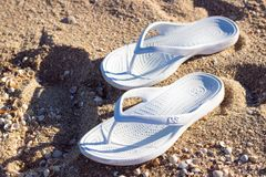 White slippers on the hot Sea, beach sand. Flip flops. White slippers on the hot Sea, beach sand royalty free stock photography