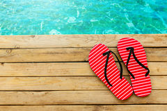 Flip flops on wooden deck over water background. Flip flops on wooden deck over water summer background royalty free stock photo