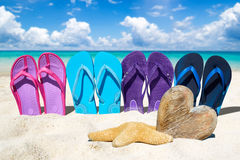 Flip flops and wooden heart on the beach. Colorful flip flops in a row and a wooden heart with copy space on the sunny beach Royalty Free Stock Photos