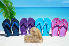 Flip flops and wooden heart. Some colorful flip flops in a row in front of a wooden heart with copy space on the sunny beach Royalty Free Stock Photography