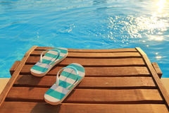 Flip flops on wooden sunbed. And water Stock Photo