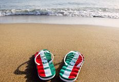 Flip flops with the word Italy on beach sand - holidays and relaxation concept Royalty Free Stock Image