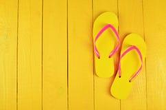 Flip Flops Yellow auf einem gelben hölzernen Hintergrund stockfoto