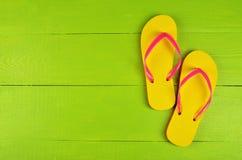 Flip Flops Yellow auf grünem hölzernem Hintergrund stockfoto