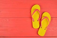 Flip Flops Yellow auf rotem hölzernem Hintergrund stockfotografie
