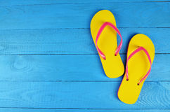 Flip Flops Yellow on blue wooden background. Flip Flops Yellow on wooden background royalty free stock photo