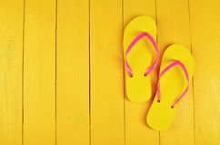 Flip Flops Yellow on a yellow wooden background. Flip Flops Yellow on yellow wooden background Stock Photo