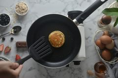 Flip the pancakes with a spatula. Concept of Cooking ingredients and method on white marble background, Dessert recipes and. Homemade stock photo