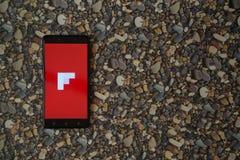 Flipboard-Logo auf Smartphone auf Hintergrund von kleinen Steinen Lizenzfreie Stockfotografie